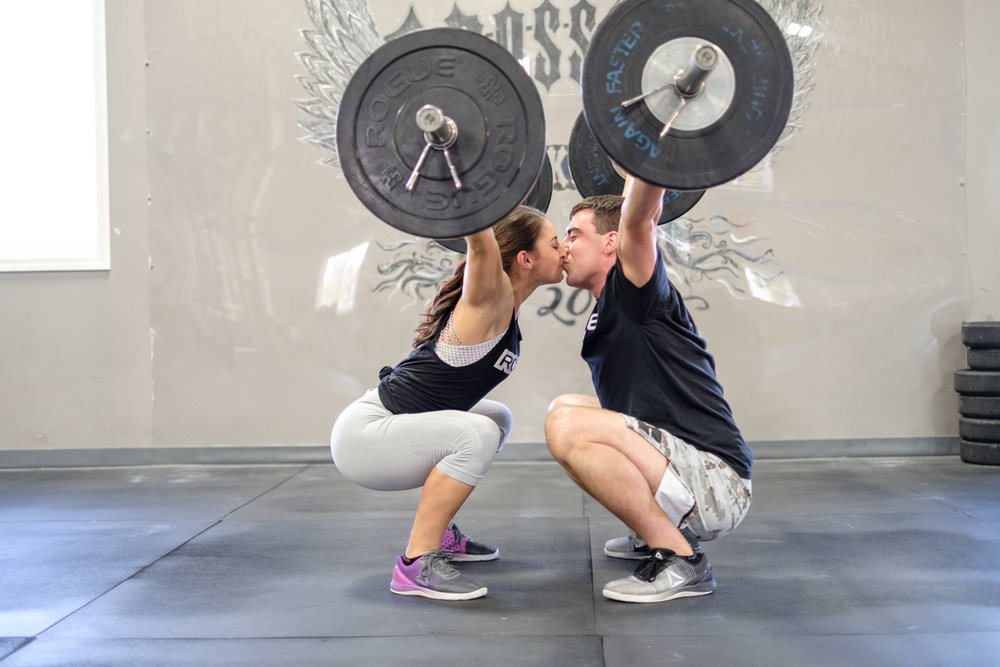 dual overhead press with couple kissing during lift at CrossFit Rockford