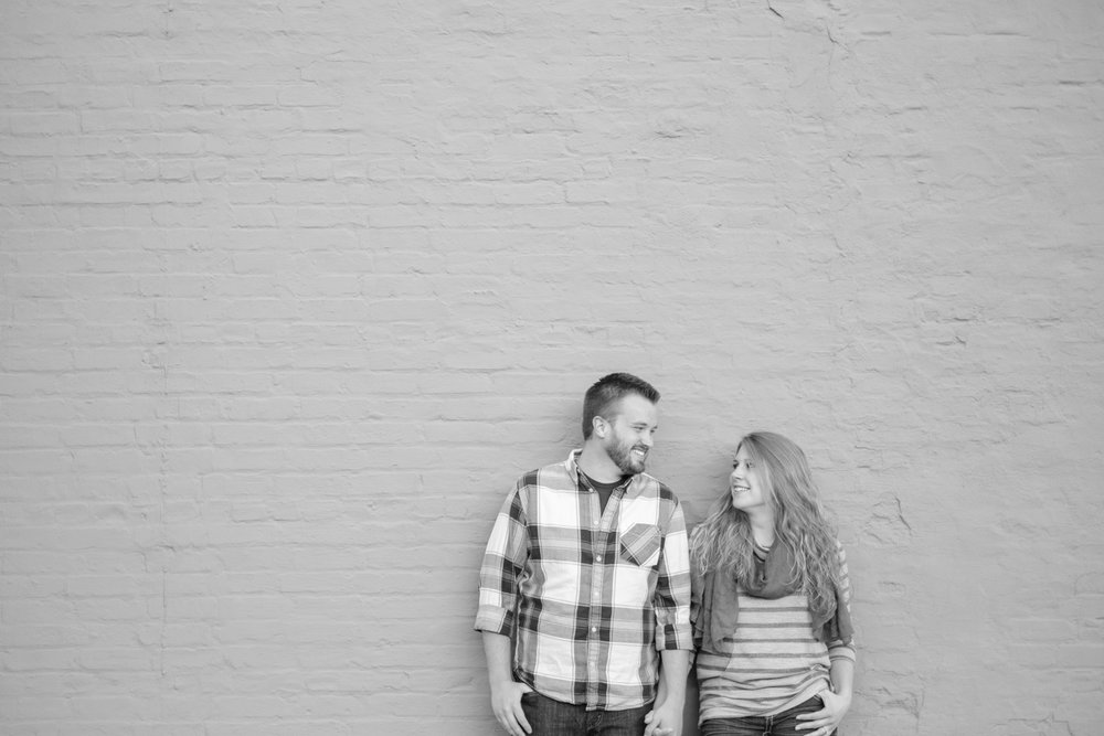 couple laughing with each other in front of painted brick wall in downtown rockton illinois