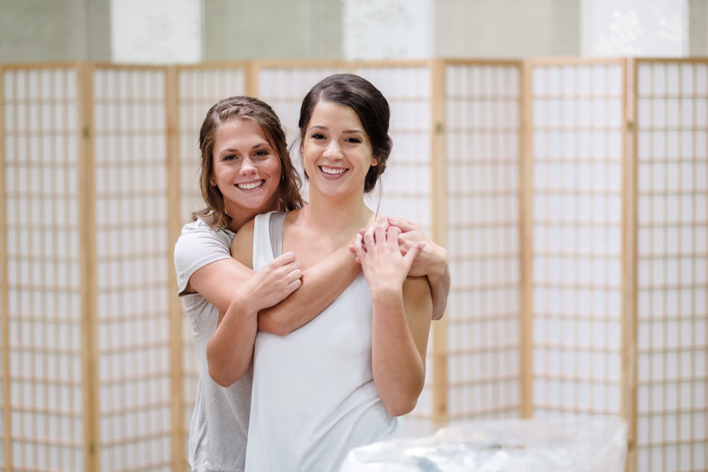 Bride and sister embrace while getting ready for her wedding at anderson japanese gardens