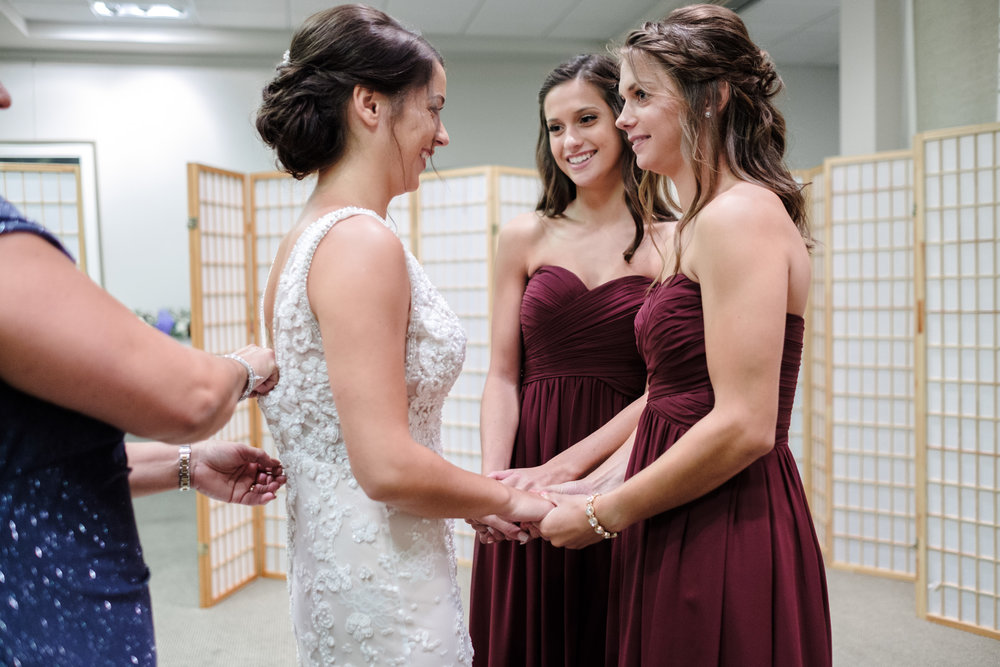 bride and sisters hold hands and say a prayer before wedding in rockford illinois photographer