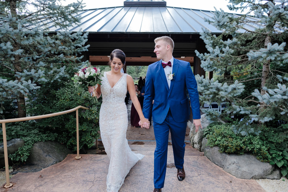 Couple joyfully walks hand in had after being just married under the pavilion at Anderson Japanese Gardens in Rockford, Illinois
