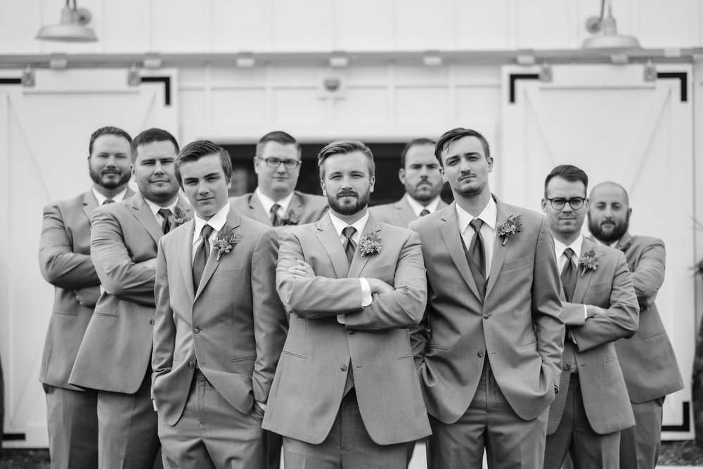 black and white photo of groom and groomsmen making best GQ face
