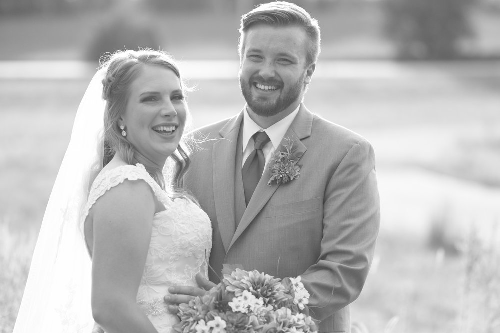 Black and white photo of bride and groom laughing on their wedding day at The Fields Reserve