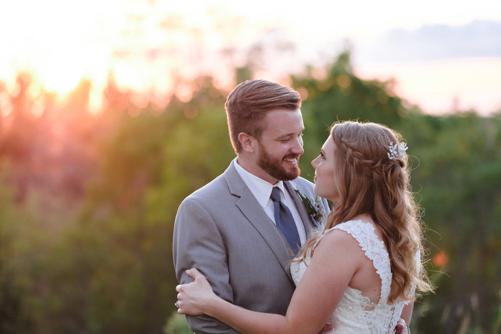 Bride and Groom lovingly embrace at The Fields Reserve in Stoughton, Wisconsin after their wedding ceremony as sunsets behind them