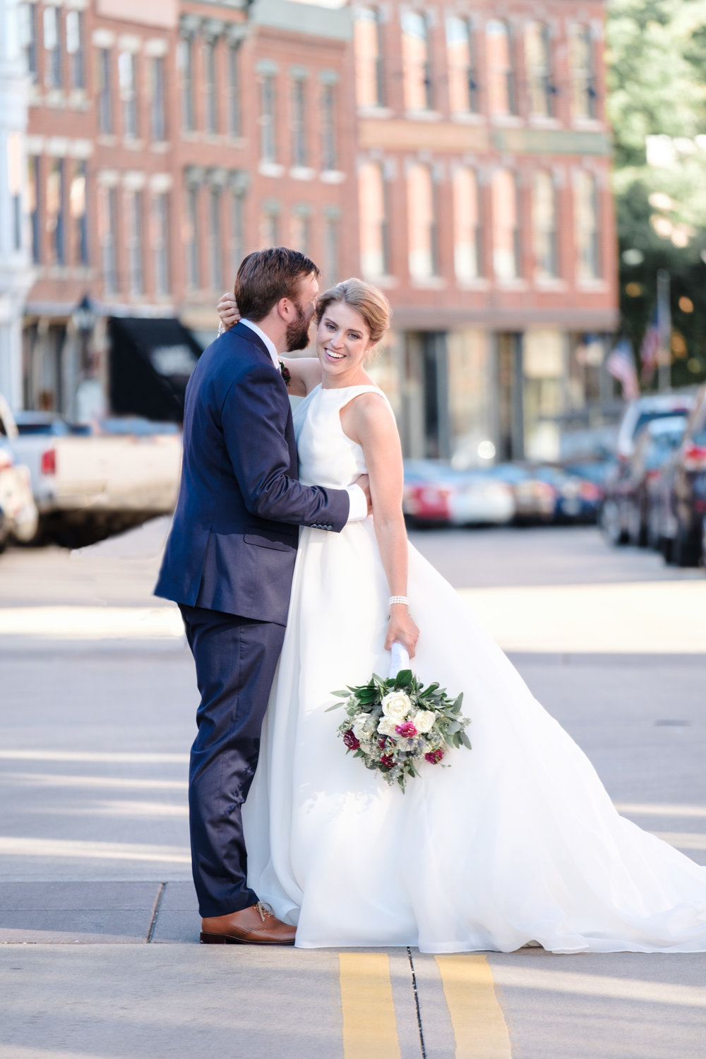 Bride and groom embracing and laughing in the middle of main street in historic Galena, Illinois