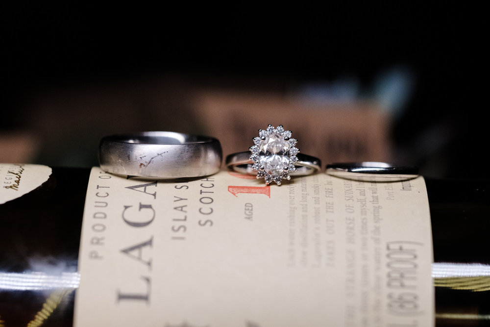 Detail shot of bride and grooms rings on Lagavulin single malt scotch.