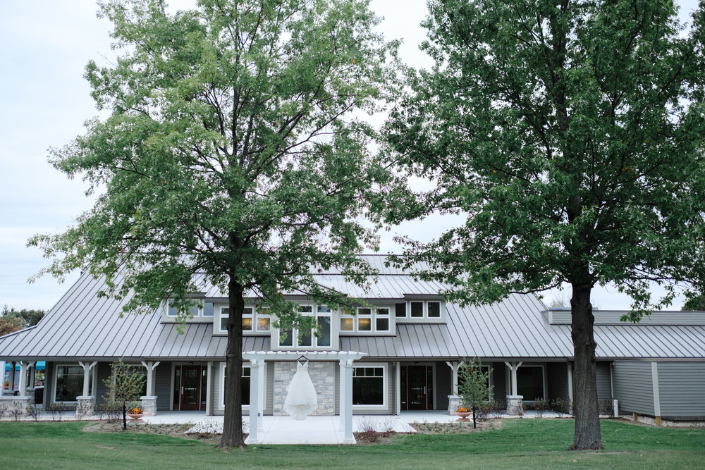 Dress hanging on pergola with pavilion in background framed by trees at Rockford Bank and Trust Pavilion.