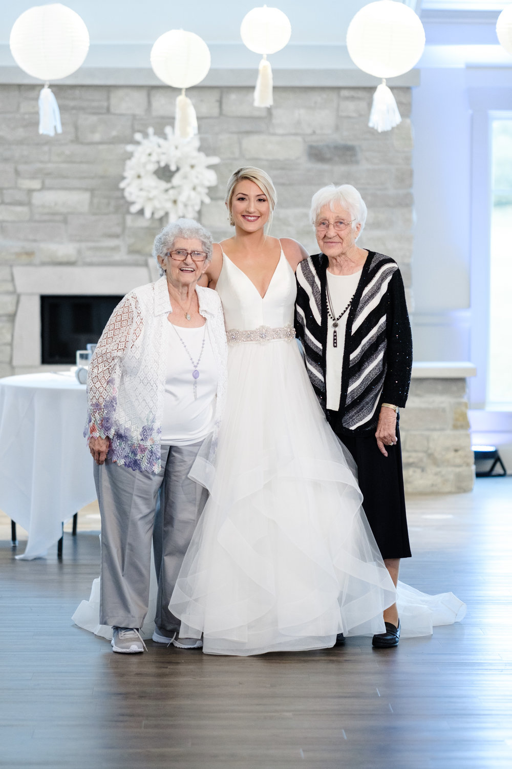Bride embracing grandmothers in front of fireplace at Rockford Bank and Trust Pavilion.