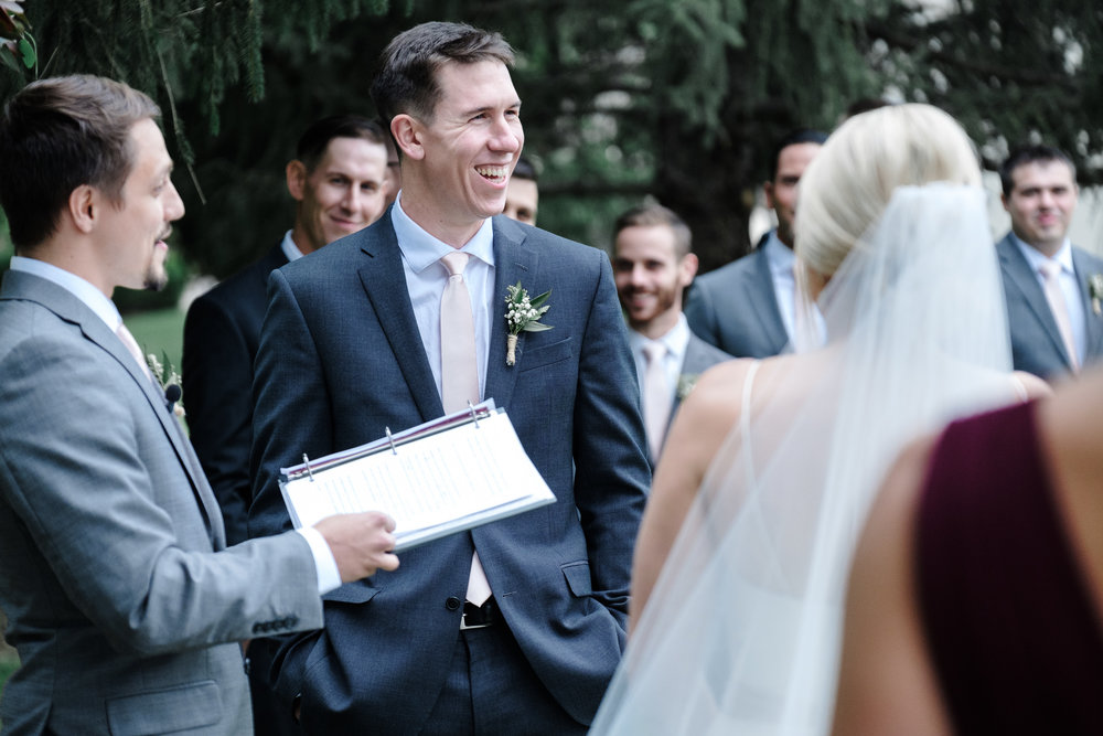 Groom laughing during vows at Rockford Bank and Trust Pavilion.