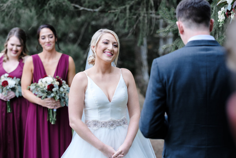 Bride laughing and smiling at groom during vows at Rockford Bank and Trust Pavilion.