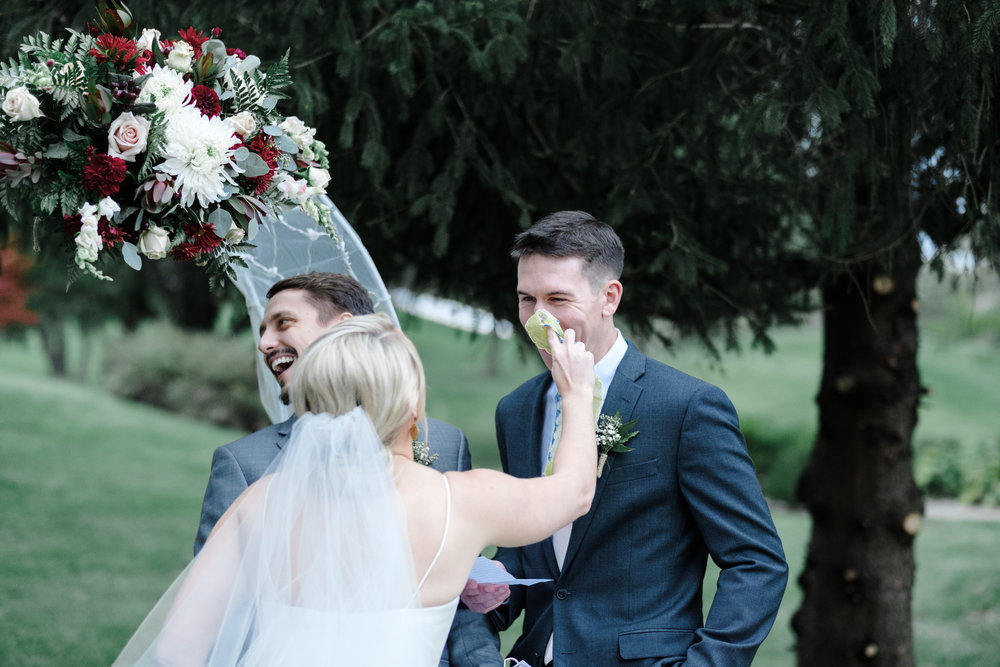 Bride wiping tears away from groom as he reads his vows at Rockford Bank and Trust Pavilion.