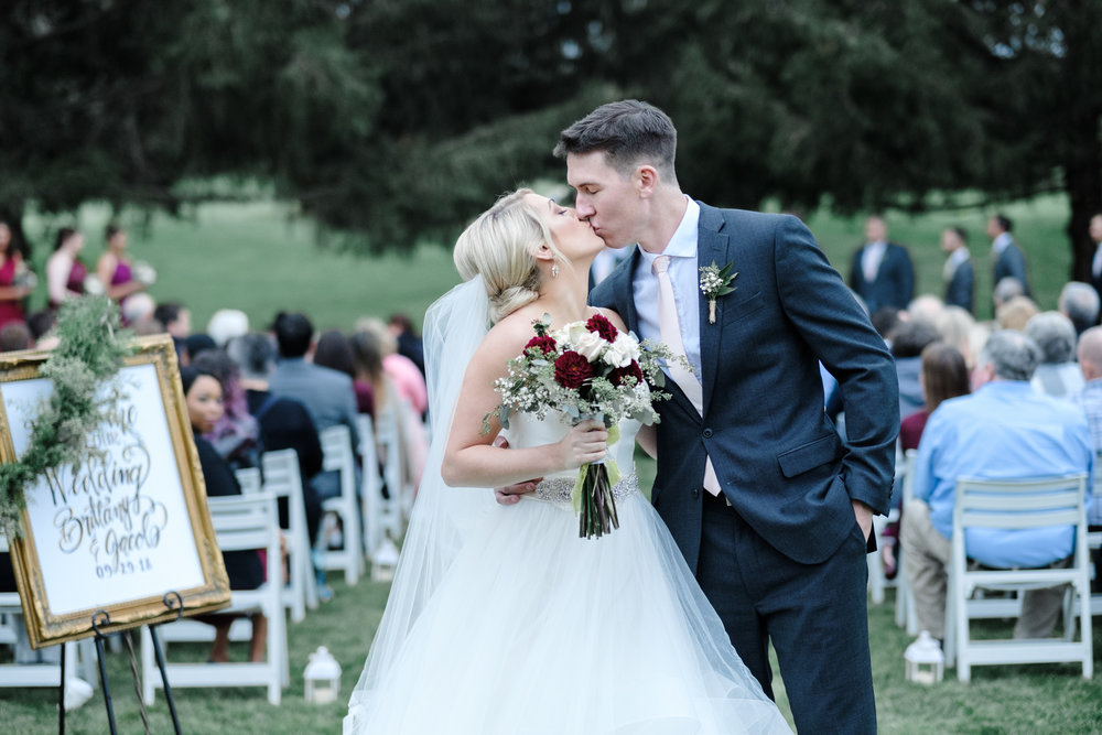 Gorgeous blonde bride kissing groom after outdoor ceremony at Rockford Bank and Trust Pavilion.