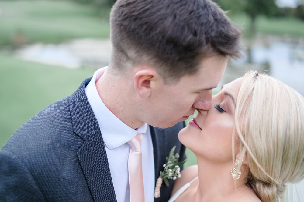 Bride and Groom kiss amongst the trees at Aldeen golf course at Rockford Bank and Trust Pavilion.