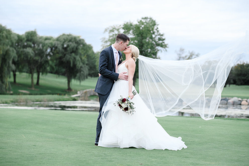 Bride and groom kissing with brides veil blowing in the wind at The Rockford Bank and Trust Pavilion