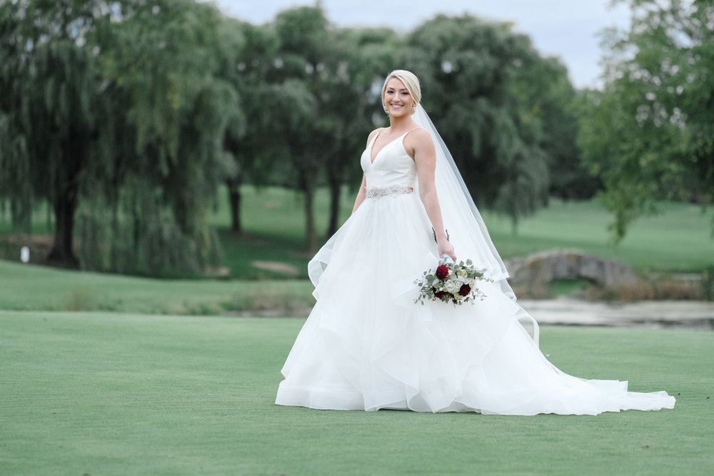 Portrait of just bride laughing at ALdeen golf course at Rockford Bank and Trust Pavilion.