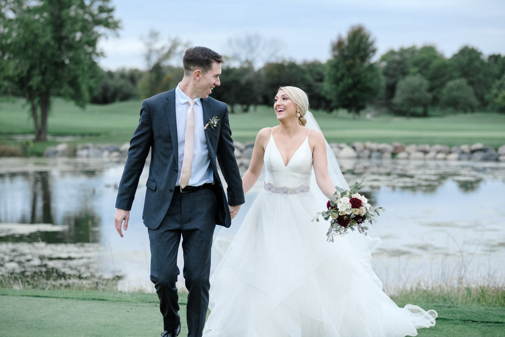 Bride and groom running while laughing at Rockford Bank and Trust Pavilion.