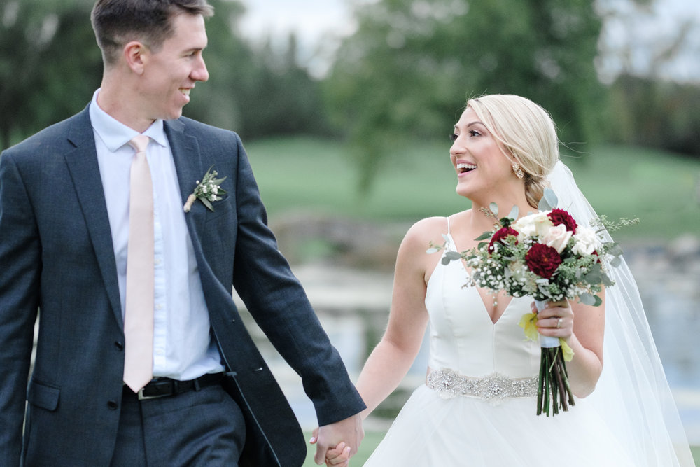 Bride and Groom holding hands while walking and laughing candidly at Rockford Bank and Trust Pavilion.