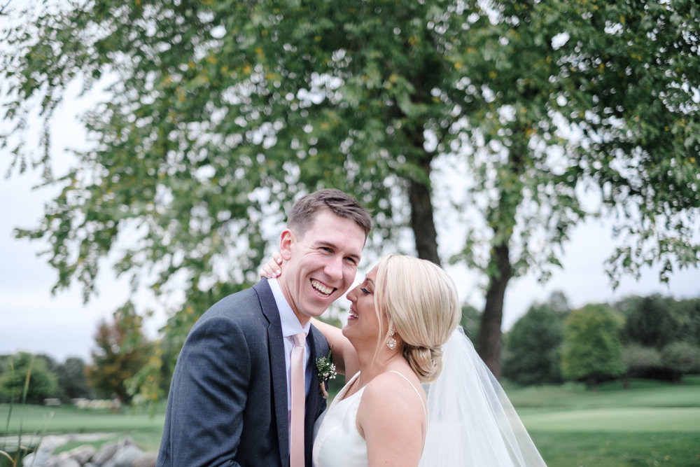 Groom laughing as bride whispers in his ear at Rockford Bank and Trust Pavilion.