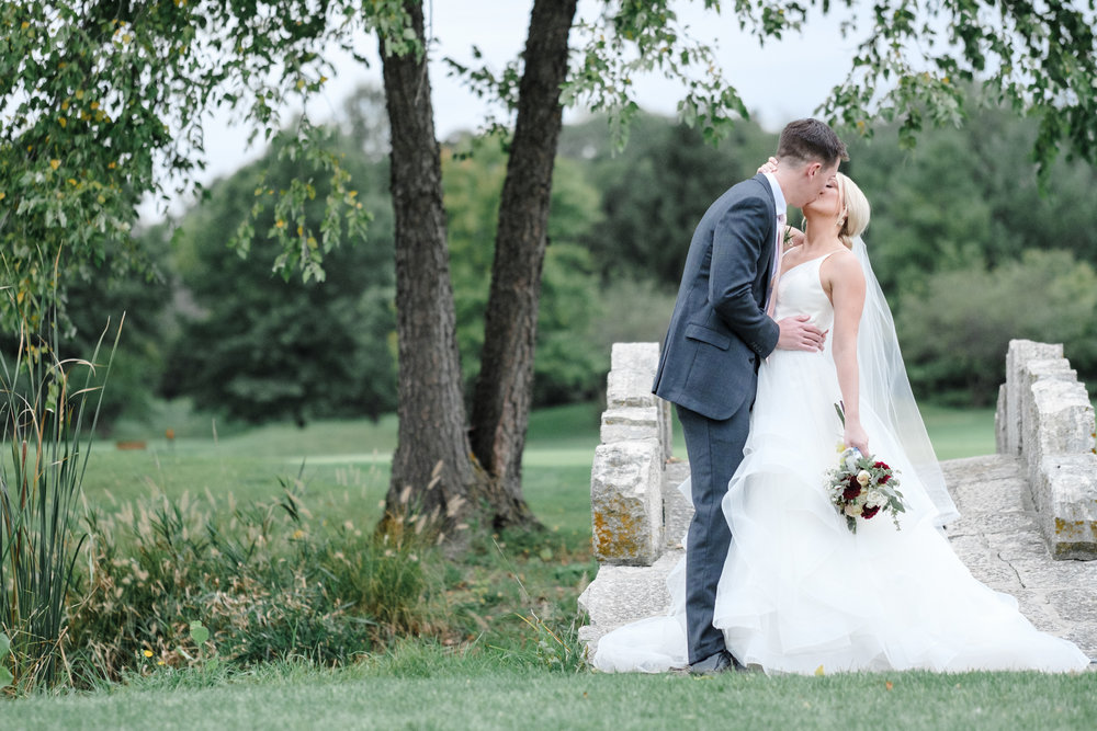 Bride and groom kissing under willow tree near stone bridge at Rockford Bank and Trust Pavilion.