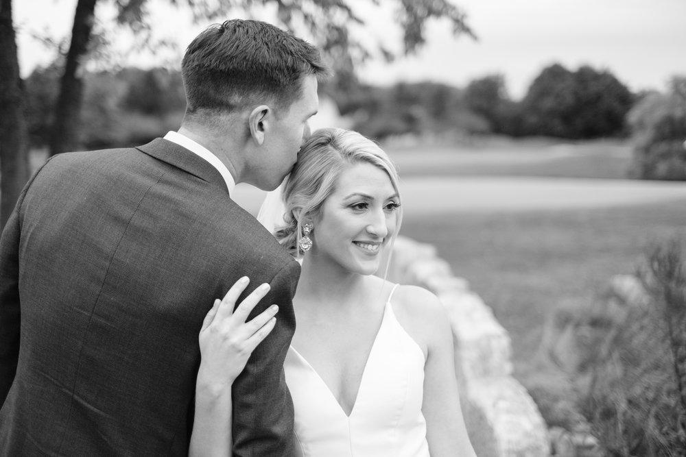 Groom kissing bride's head on bridge at Aldeen golf course for their wedding at Rockford Bank and Trust Pavilion.