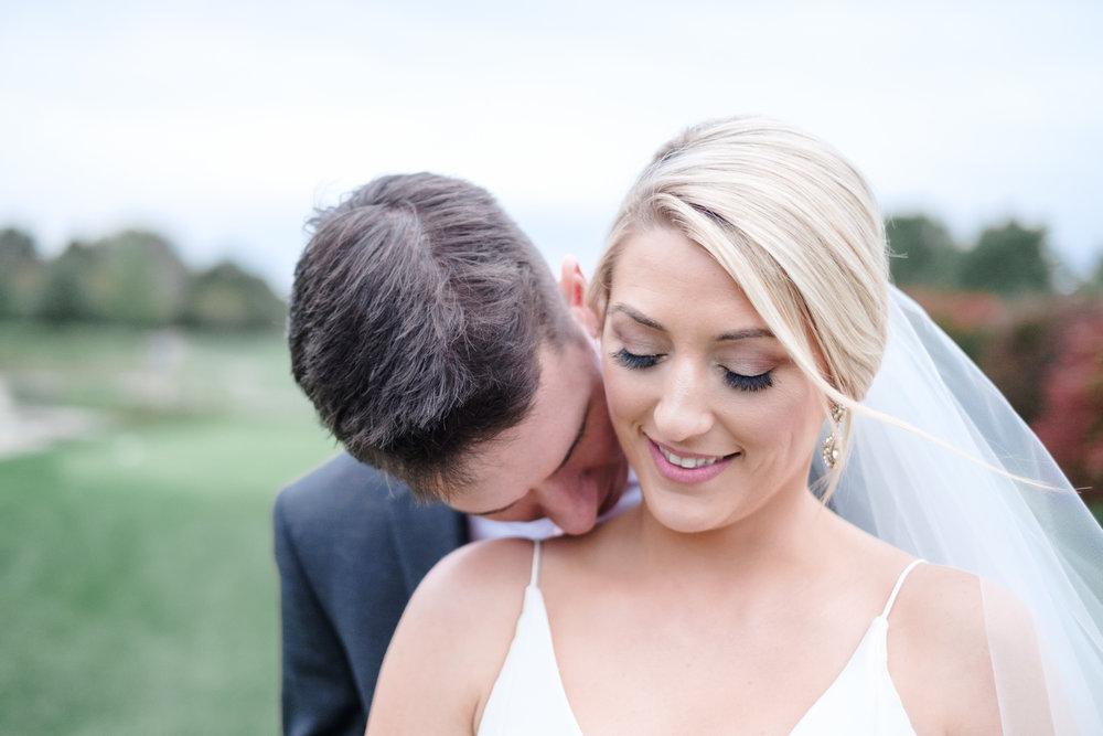 Groom kissing blonde brides neck at Rockford Bank and Trust Pavilion.
