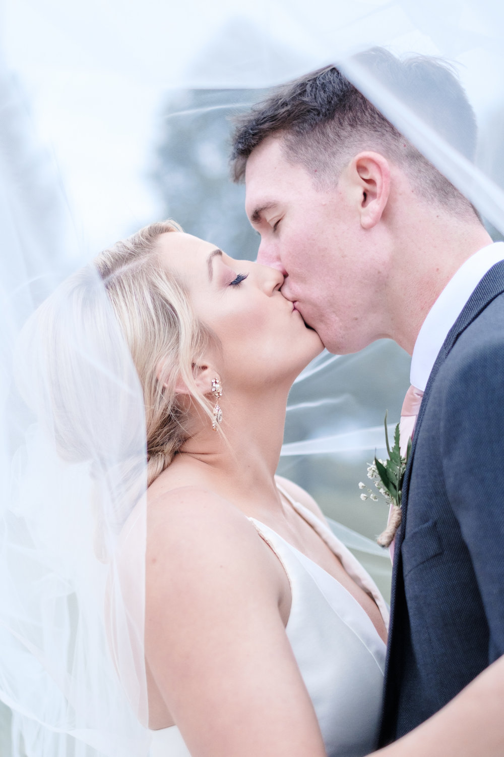 Bride and groom kissing under veil at Rockford Bank and Trust Pavilion in Rockford, Illinois.