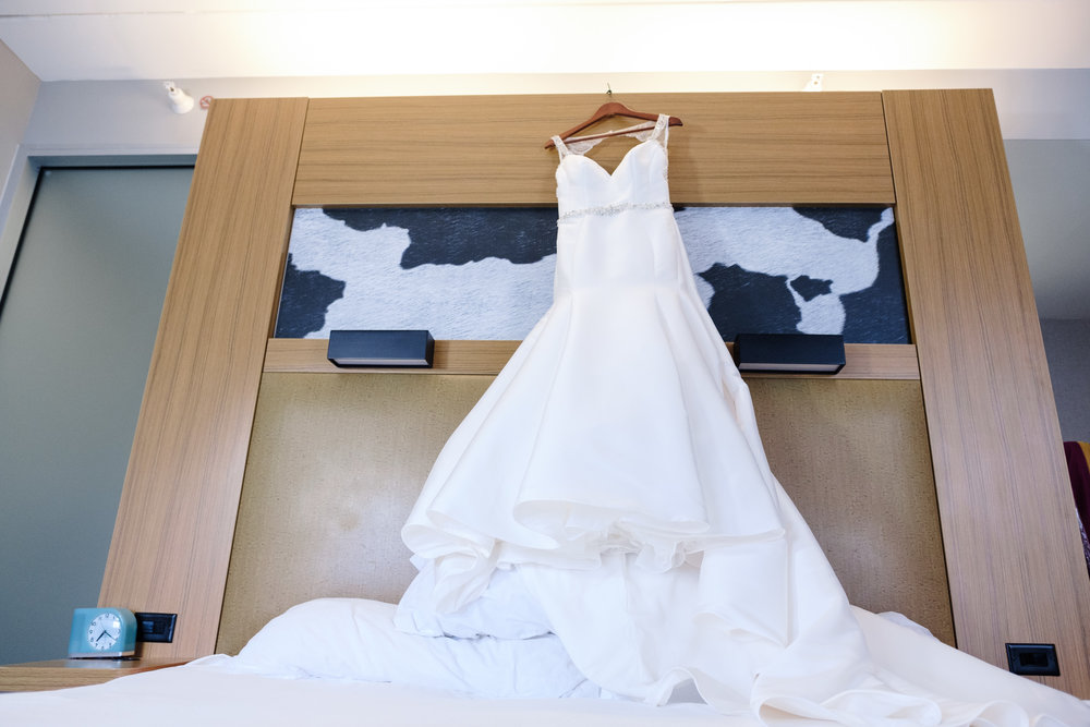 brides dress hanging above bed in hotel before Rockford wedding