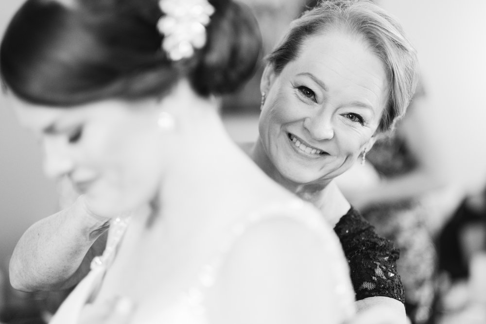 brides mom helping her get into her wedding dress