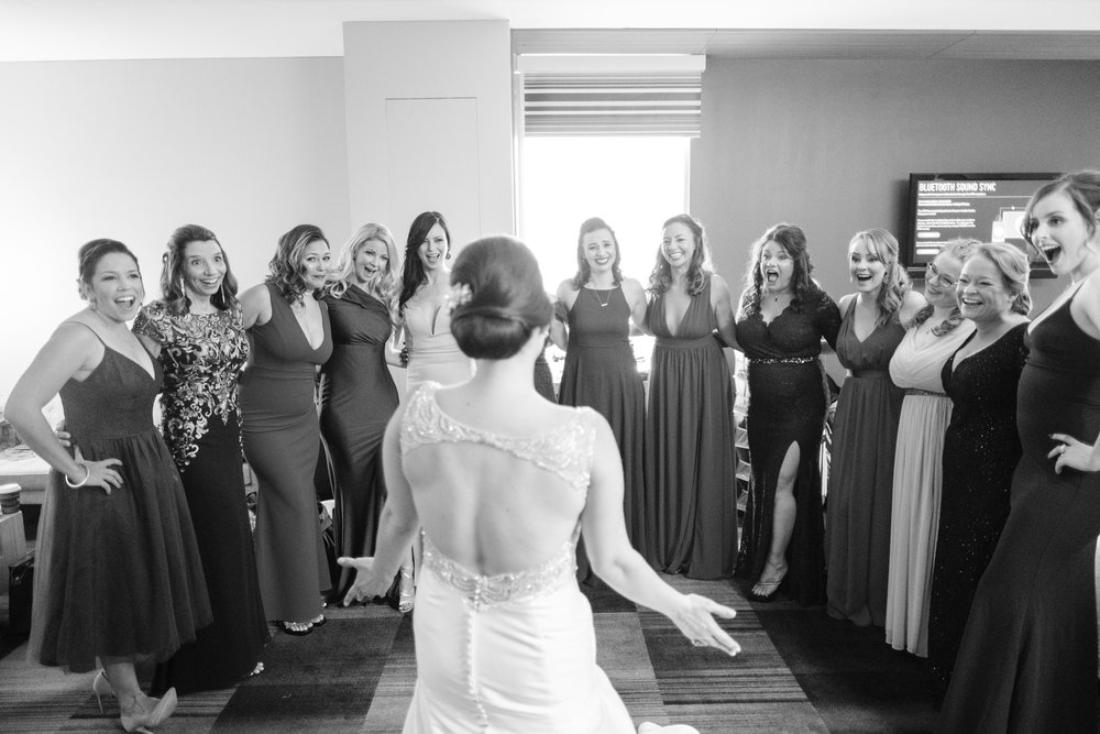 bride joyfully showing off her dress to her best friends on her wedding day