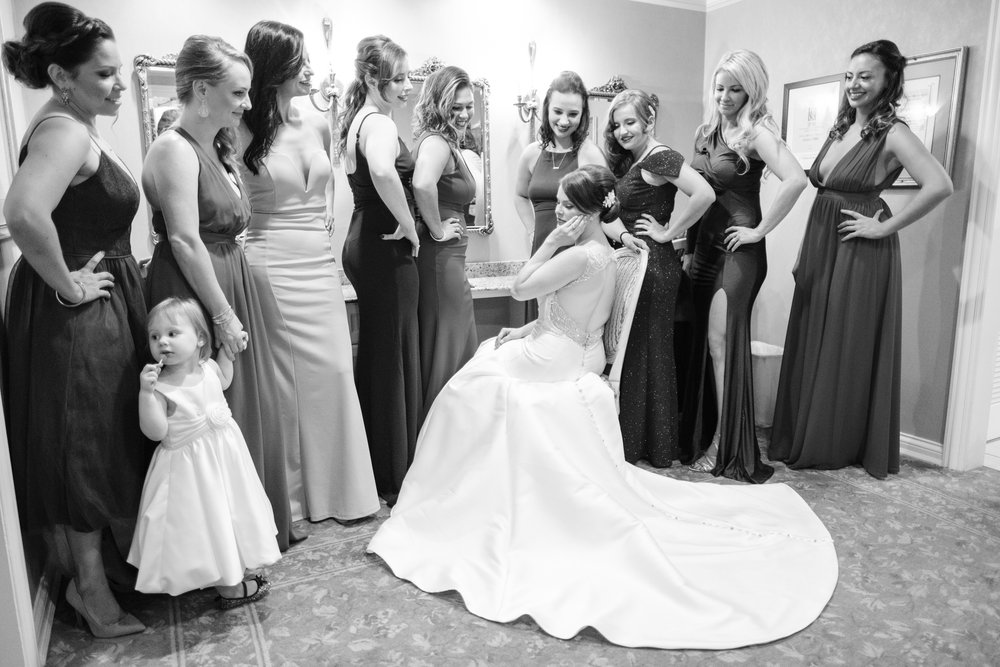 finishing touches of bride surrounded by bridesmaids at cog hill golf club