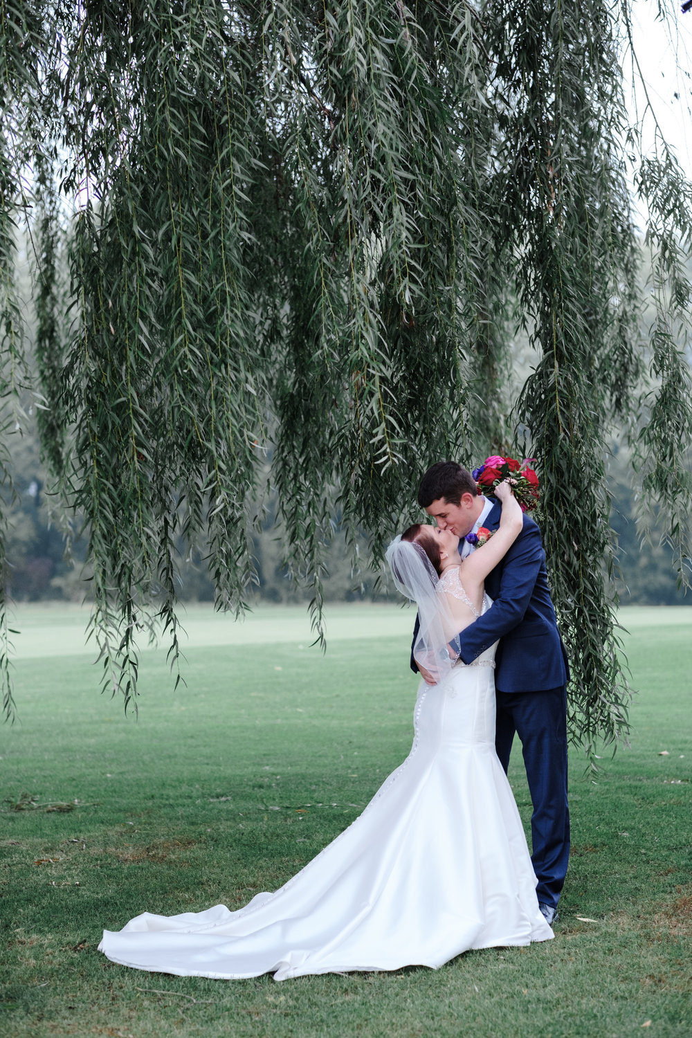 bride and groom hug under willow tree on cog hill golf course for portraits