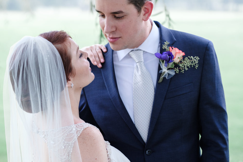 bride and groom stare into each others eyes for a candid portrait with him in blue suit