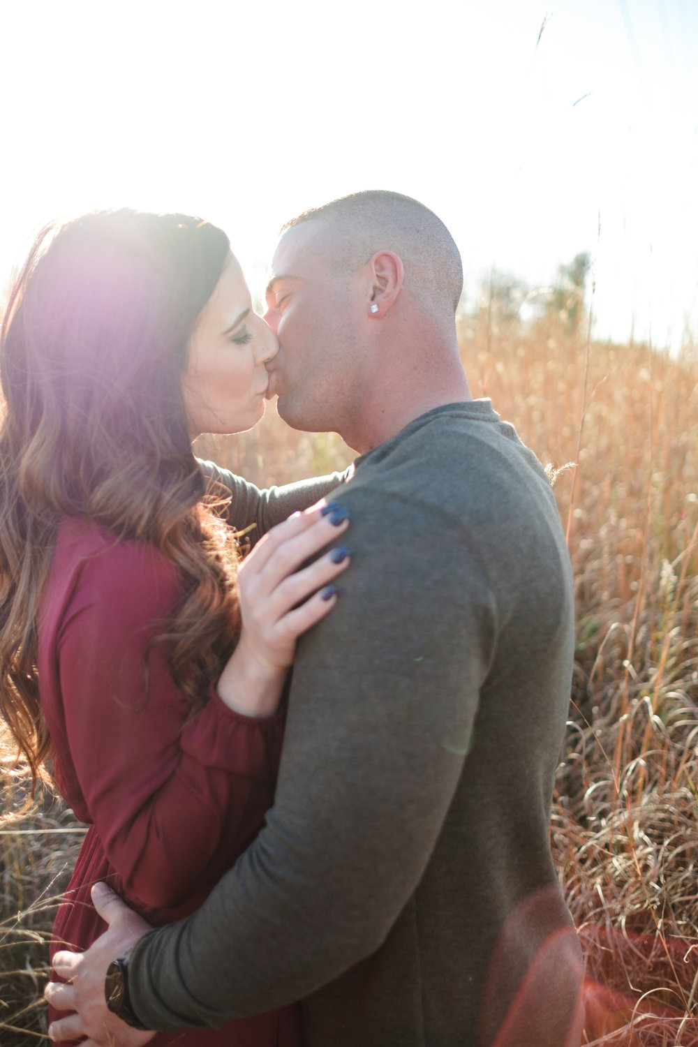 Couple kiss during engagement session at golden hour with sun setting behind them at Rock Cut State park in rockford illinois.  Wedding Photographer