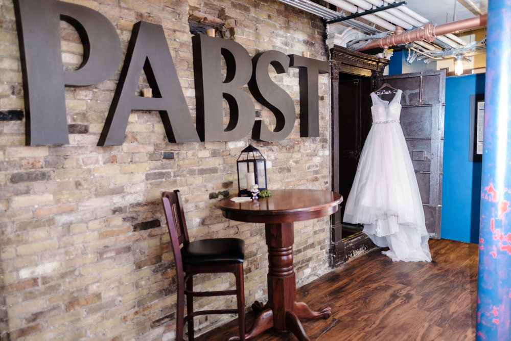Brides wedding dress hanging on jail cell door next ot Pabst sign.