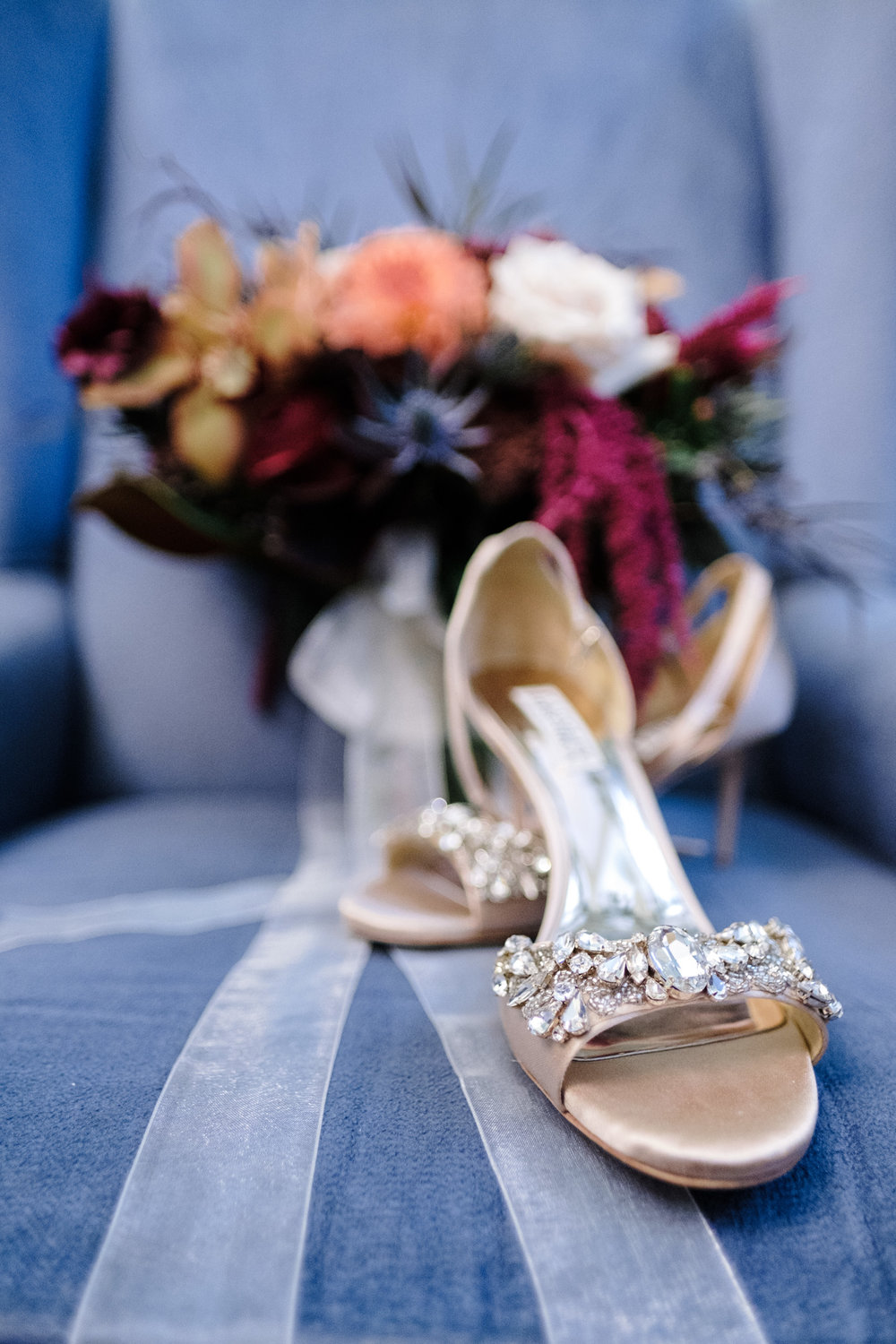 Fall florals and diamond encrusted heals for the bride rest on a blue suede chair at Pabst Best Place in Milwaukee Wisconsin for a fall wedding