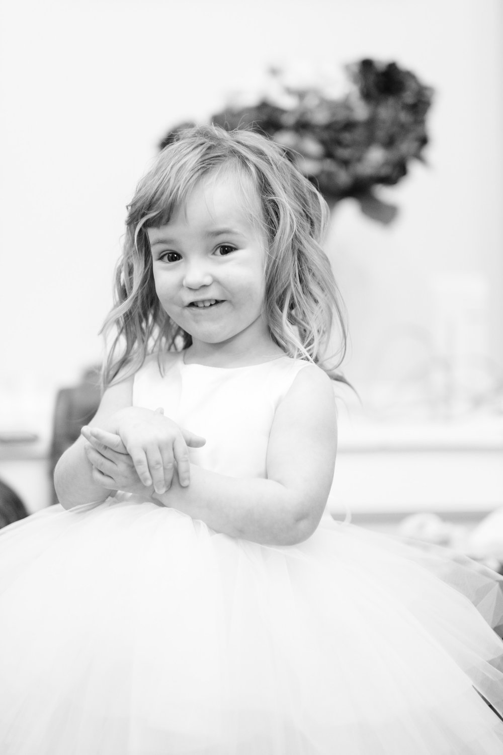 Flower girl smiling while looking at bride in her wedding dress in black and white at pabst best place in milwaukee, wi.