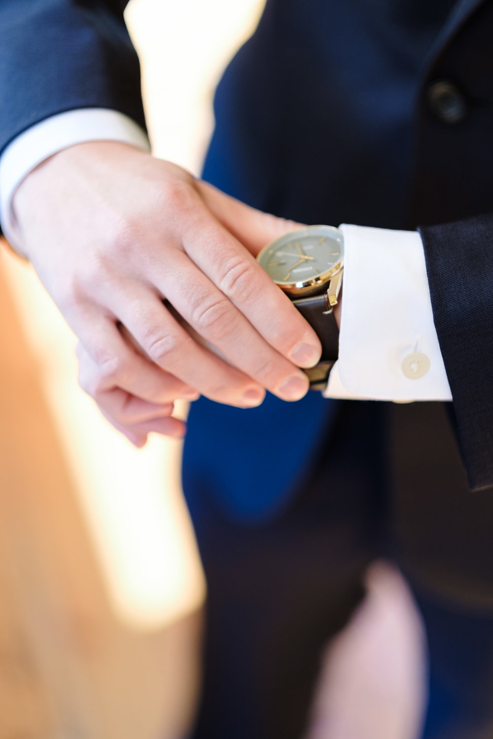 Groom adjusting watch with blue suit on by rockford wedding photographer b. adams photography