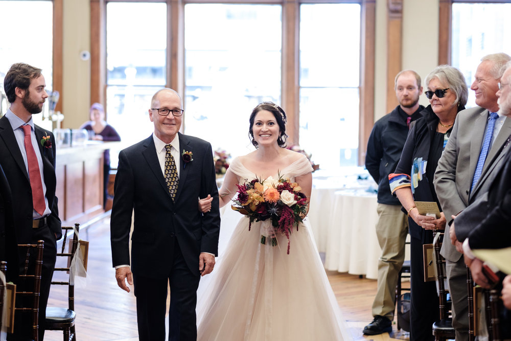 Candid wedding photo of wisconsin bride walking down aisle at pabst best place.