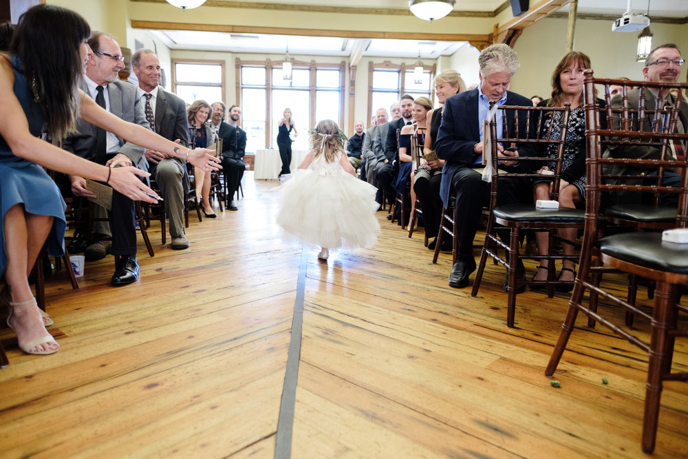 brewery wedding with flower girl running back up the aisle during wedding of wisconsin couple