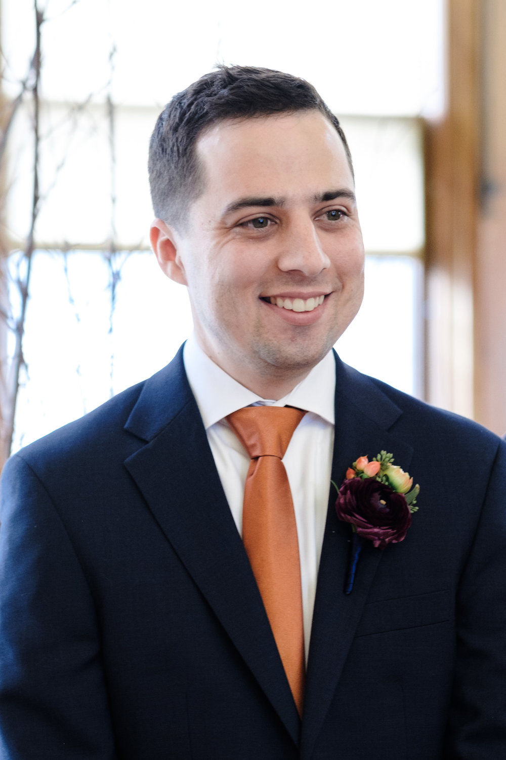 Groom in orange tie and blue suite seeing his bride for the first time at their elegant wedding.