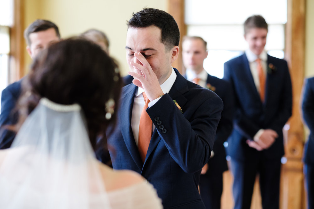 groom wipes a tear away as his bride reads her vows