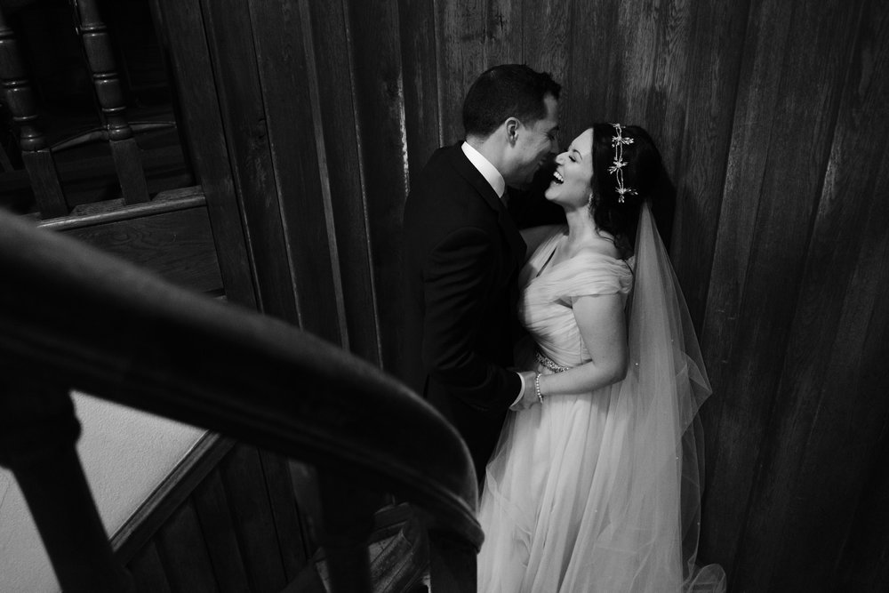 bride and groom kiss and embrace on spiral staircase at pabst best place.