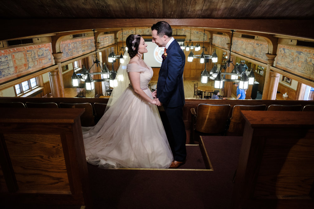 Wisconsin bride and groom at milwaukee wedding candid portrait overlooking reception hall
