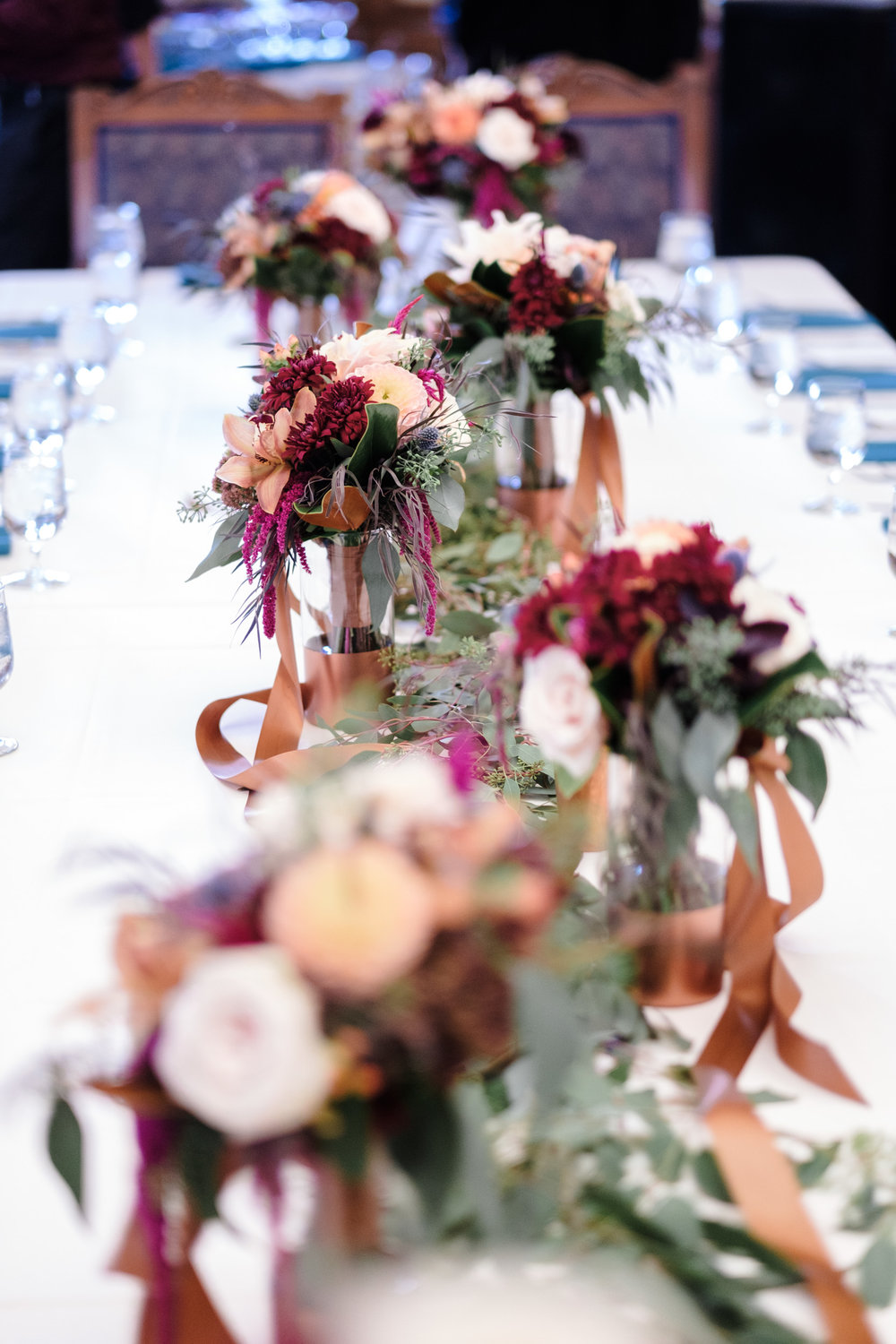 head table centerpiece of maroon, orange and mint green.