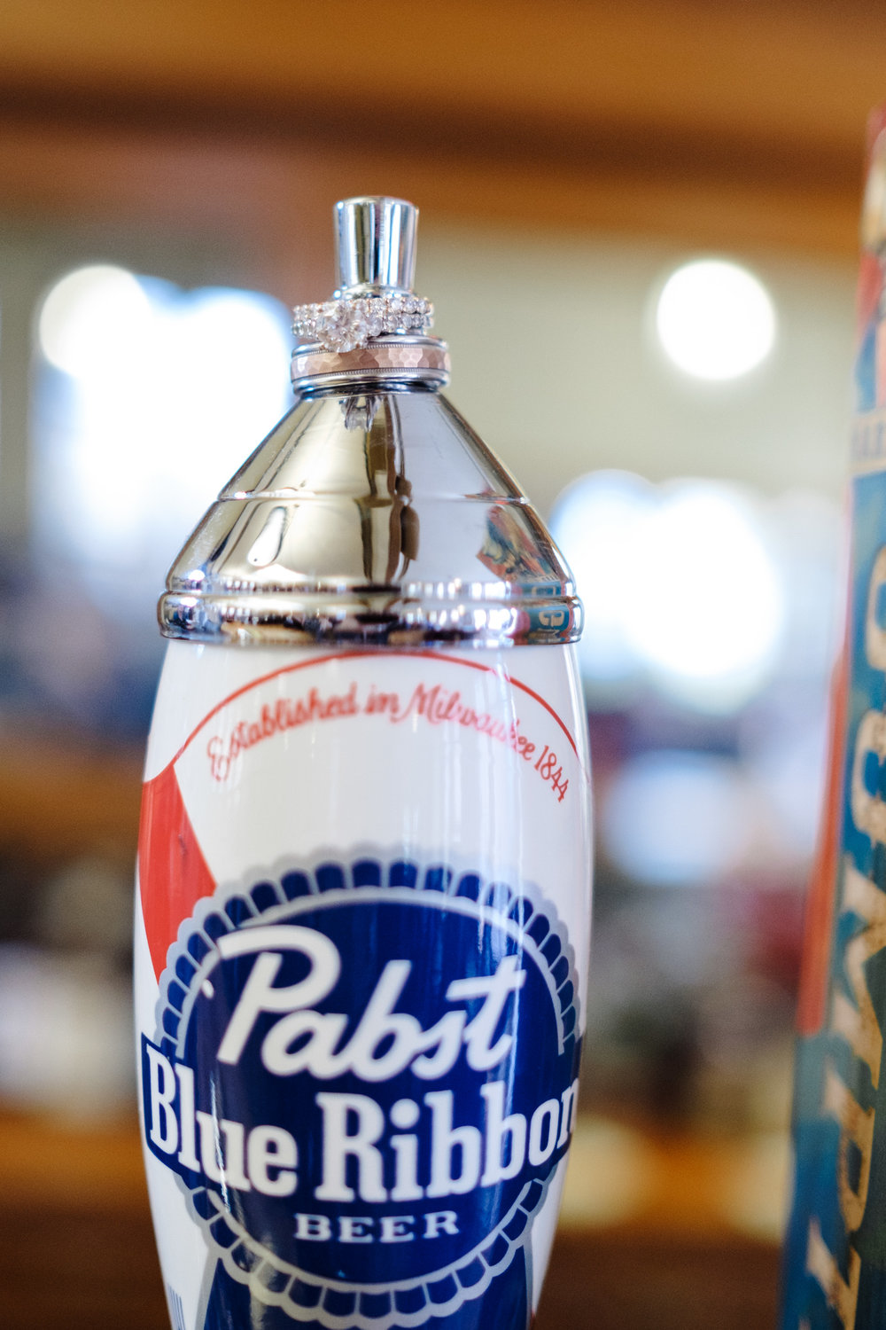 Detail ring photo of rose gold rings on pabst blue ribbon beer tap handle.