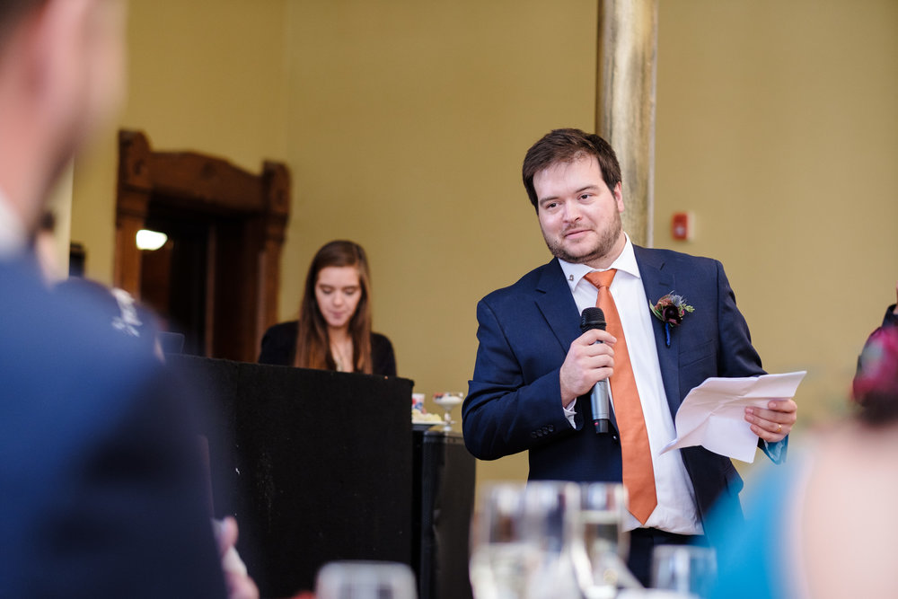 brother of the bride, mantron of honor, giving speech in blue suit and orange tie