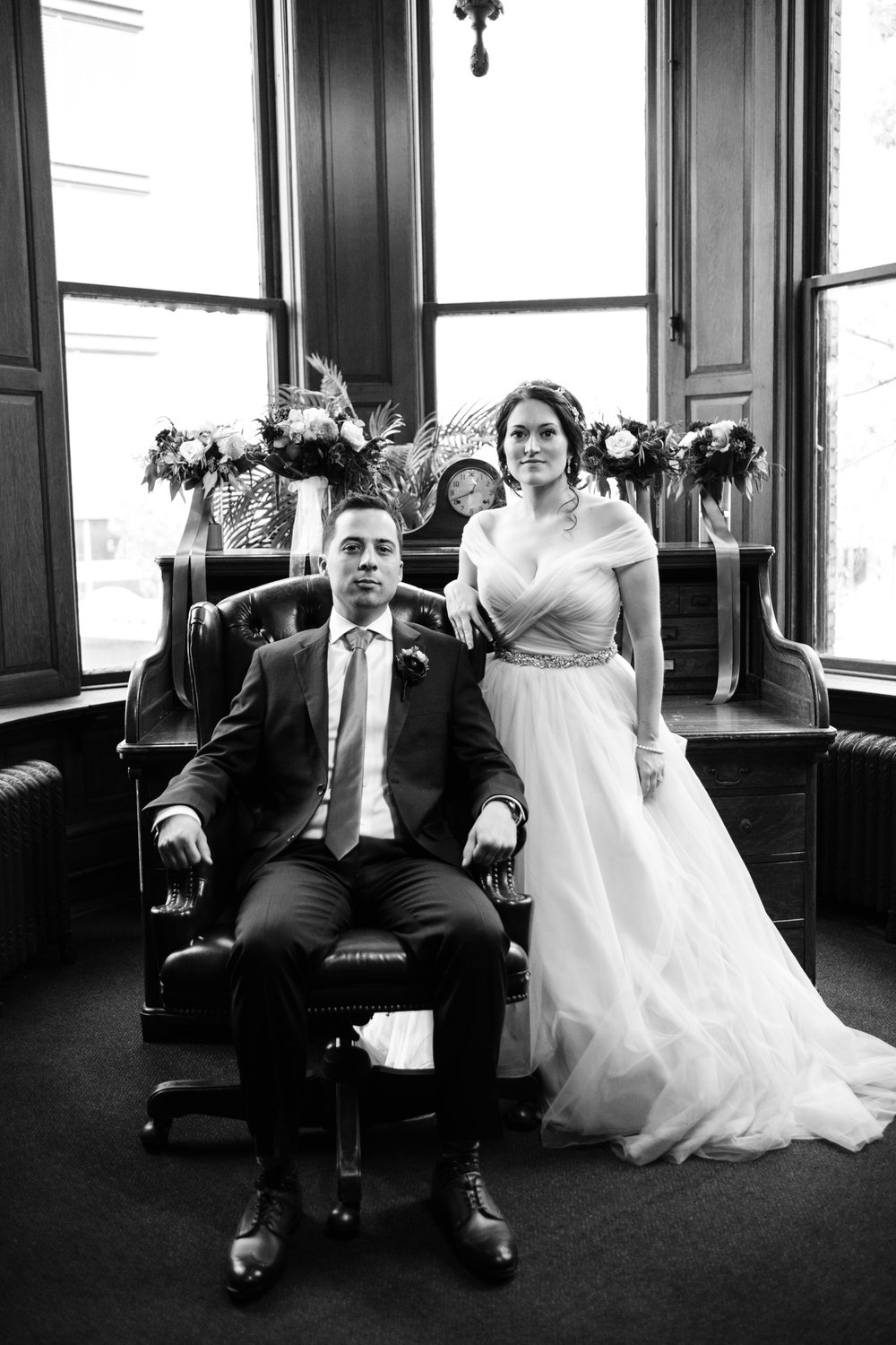 Classic black and white bride groom portrait at desk chair.  milwaukee wisconsin wedding