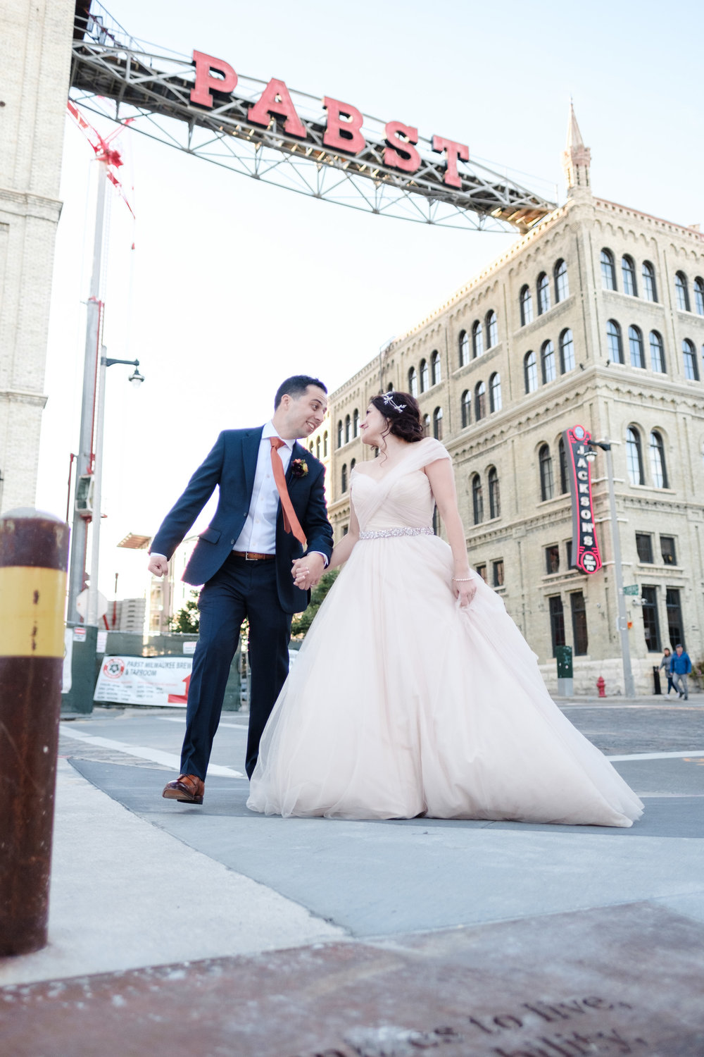 Bride and groom laugh and walk while holding hands in front of neon Pabst sign at Pabst best place in downtown Milwaukee Wisconsin.