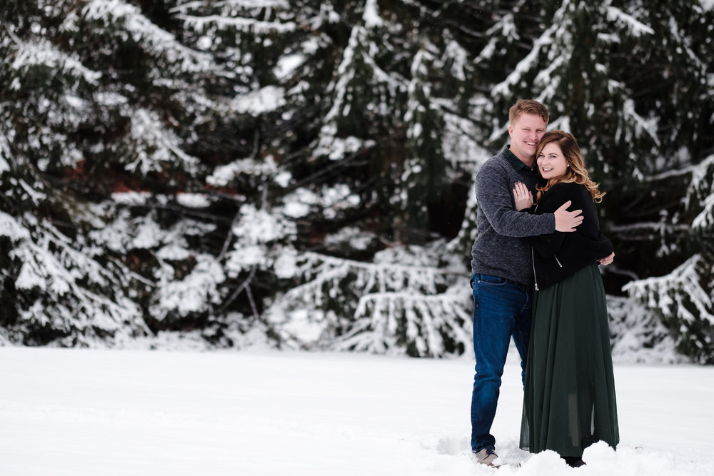 Pavilion at Orchard Ridge Farms snowy engagement. green skirt with black mini coat with snow covered pine trees