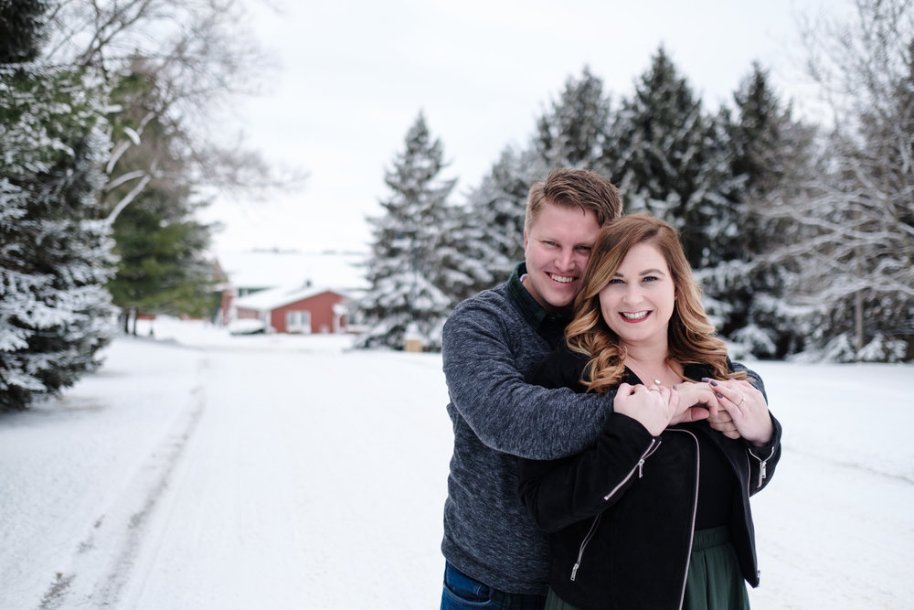 Pavilion at Orchard RIdge Farms engagement session on the snowy road leading to the pavilion